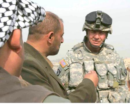 Lt. Col. Thomas Kunk, commander 1st Battalion, 502nd Infantry Regiment speaks with an Iraqi city councilman about future projects to improve the Mahmudiyah (source: DVIDS)