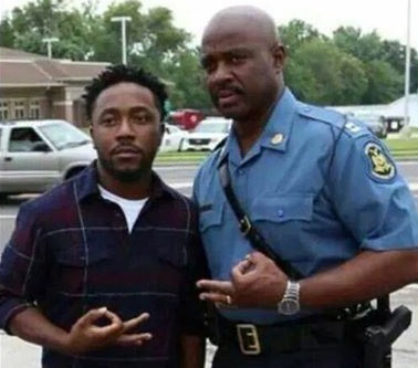 Missouri State Police Captain Ron Johnson making fraternity sign with Ferguson protestor