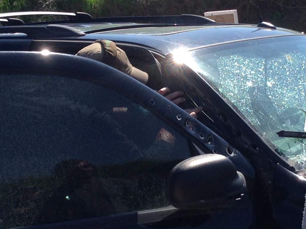 Petty inspecting damage. Some rounds penetrated and bounced off the windshield inside the vehicle.