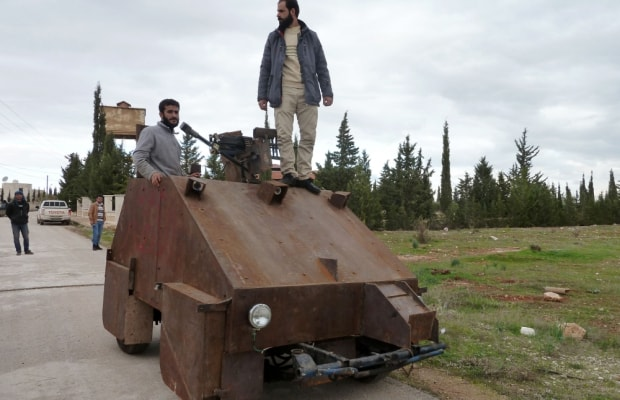 "Syrian rebels stand atop Sham II, a homemade armoured vehicle made by the rebels' Al-Ansar brigade, in Bishqatin, 4 kms west of Aleppo, on December 8, 2012. From a distance it looks rather like a big rusty metal box but closer inspection reveals the latest achievement of Syrian rebels: a homemade armoured vehicle waiting to be deployed. Sham II, named after ancient Syria, is built from the chassis of a car and touted by rebels as ""100 percent made in Syria."" AFP PHOTO/HERVE BARHERVE BAR/AFP/Getty Images"
