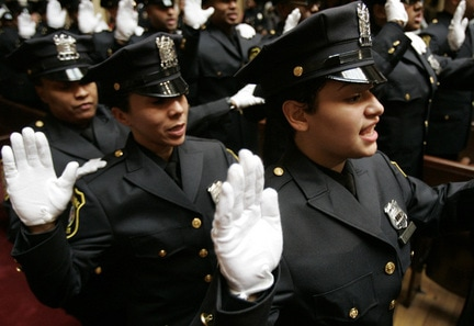 Damarie Acevedo, right, takes the oath of office at the graduation ceremony for Newark Police Department's 114th recruit class Tuesday in Newark. Fifty-eight recruits were sworn in as police officers. SARAH SIMONIS/FOR THE STAR-LEDGER