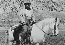 Theodore Roosevelt with one of his rifles, mounted.
