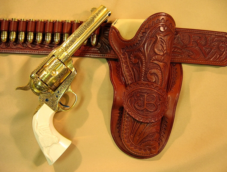 Image of a gold pistol with embossed leather holster.