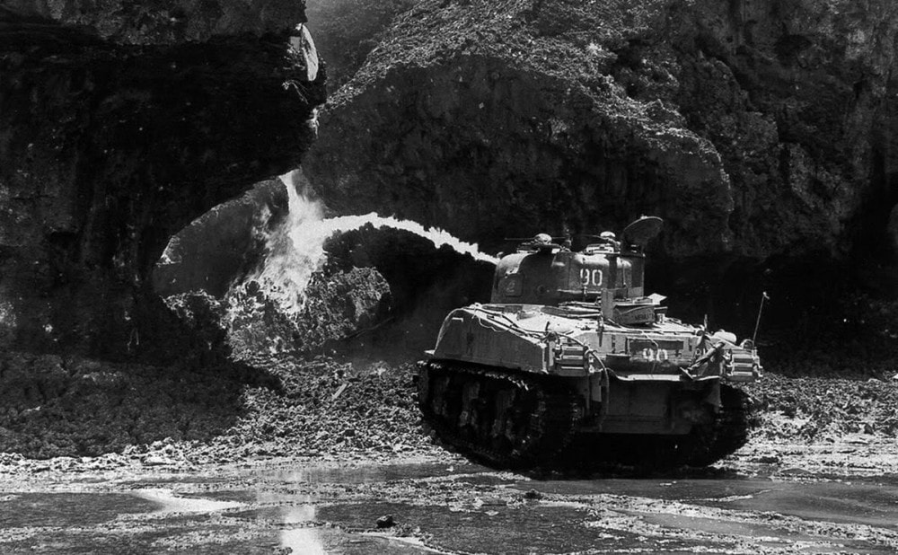 M4 Sherman flamethrower tank working crevices in the rocks along the shoreline of Okinawa.