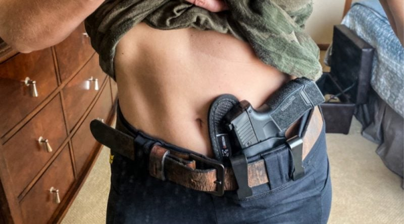 Vakandi Apparel - Women's Tactical Leggings with a Flagrant Beard Belt, and a holstered P365.