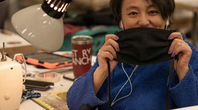 One of the seamstresses at Mystery Ranch showing off a face mask.