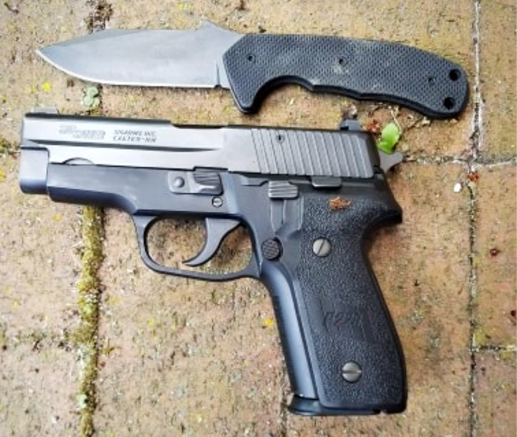 The Emerson Police Utility Knife next to a Sig P228 to illustrate just how compact the PUK is.